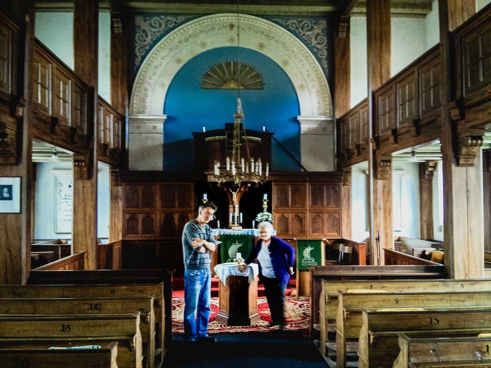 Wir werden aufgeklärt. Durch das ganze Holz ist dies die einzige Kirche unterwegs, die sich drinnen wärmer anfühlt, als draussen. Bei den anderen ist es genau anders herum.