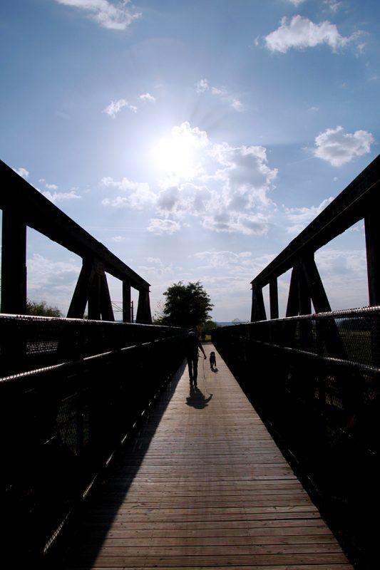 Über die Brücke der bereits tief stehenden Sonne entgegen starten meine Freunde und ich unsere Wanderung entlang der Unstrut in Artern.
