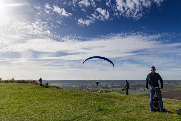 Ein Paraglider startet am Hang während auf dem Fluplatz Laucha die Segelflieger landen.