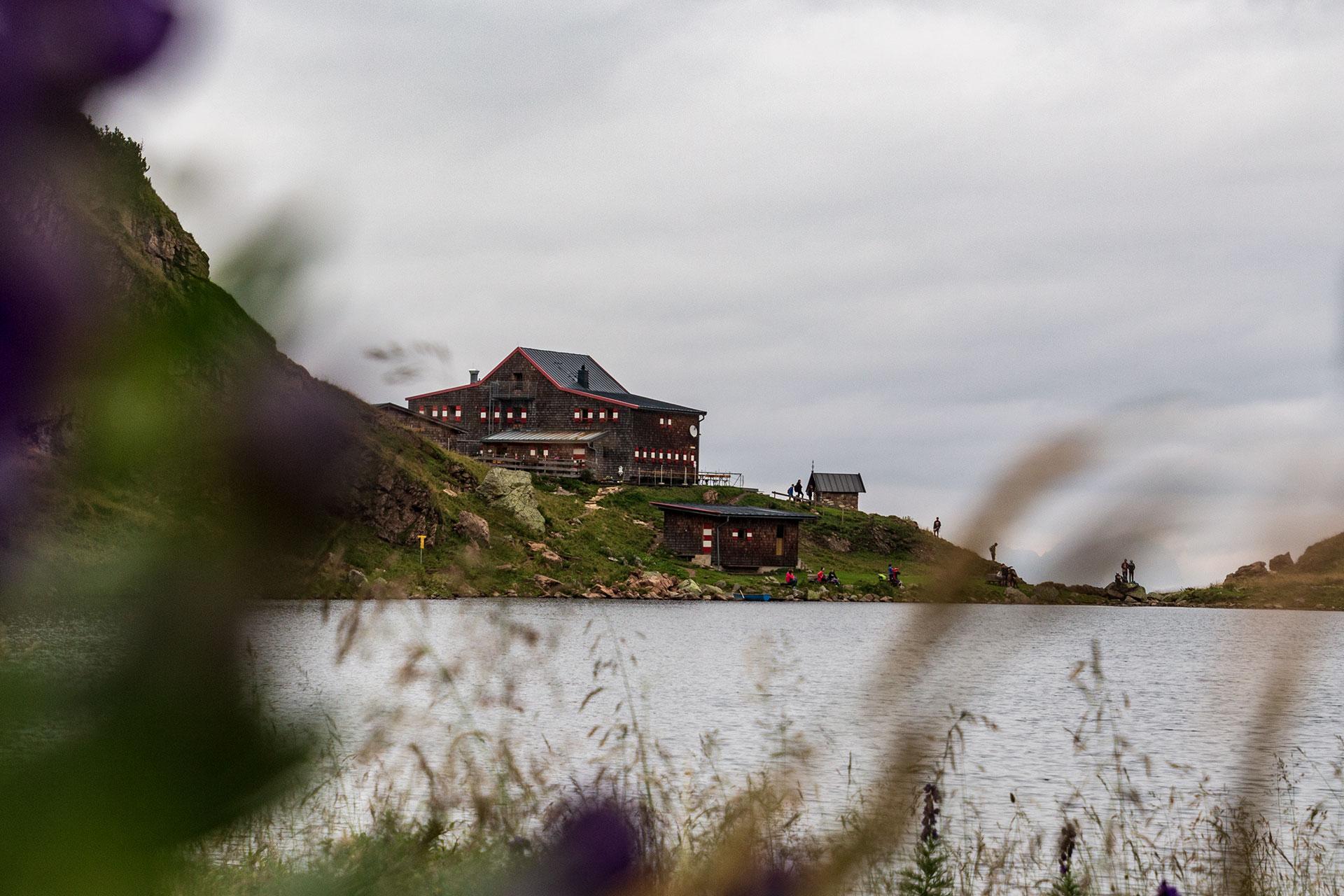 Während sich noch der Morgennebel verzieht tauchen erste Tagesgäste aus dem Tal an der Wildseeloderhütte auf.