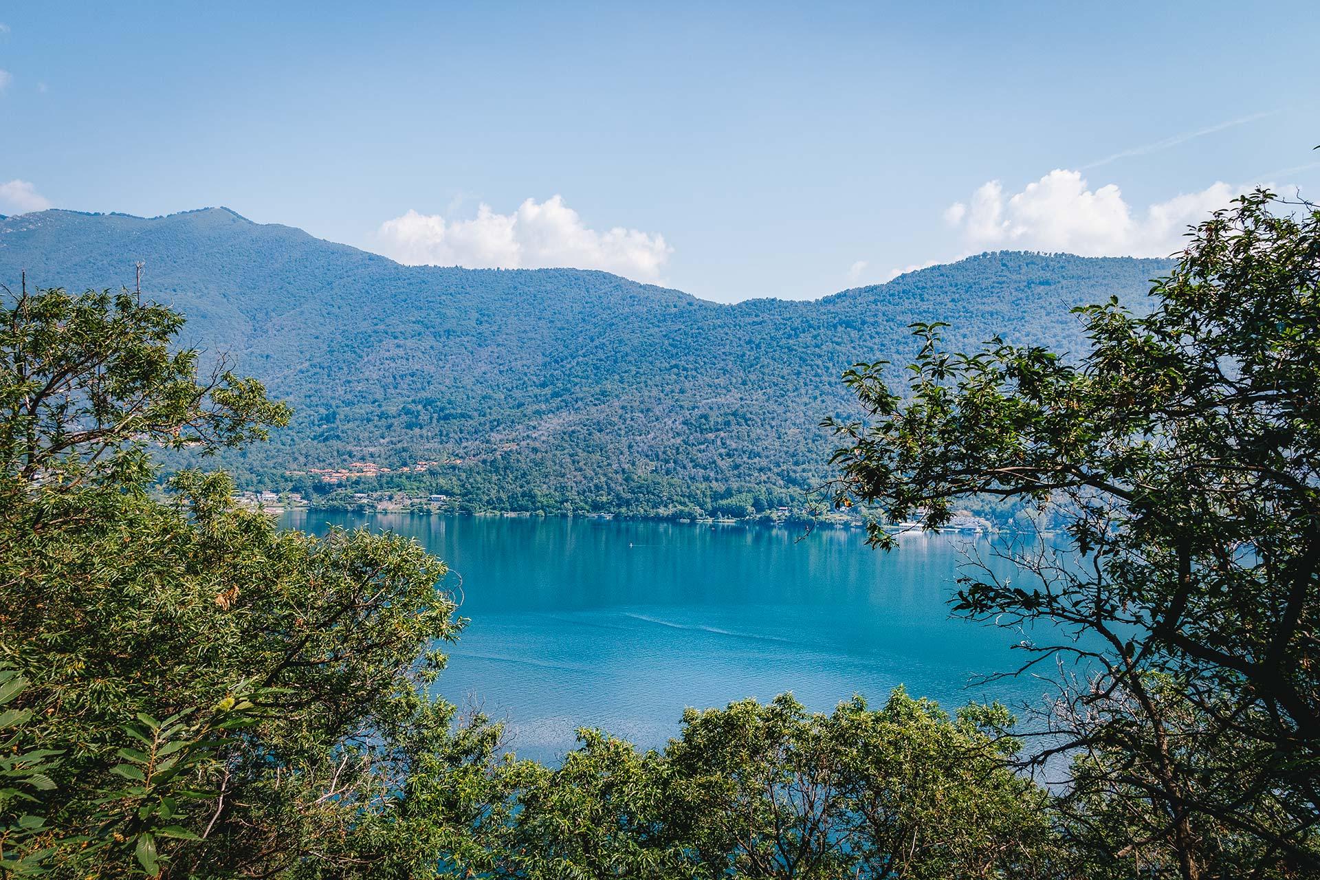 Strahlend blau schimmert der Lago di Mergozzo immer wieder durch die Bäume entlang des Steinbrecherpfads