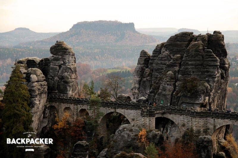 Die über die Felsen laufende Basteibrücke. Im Hintergrund der Lilienstein.