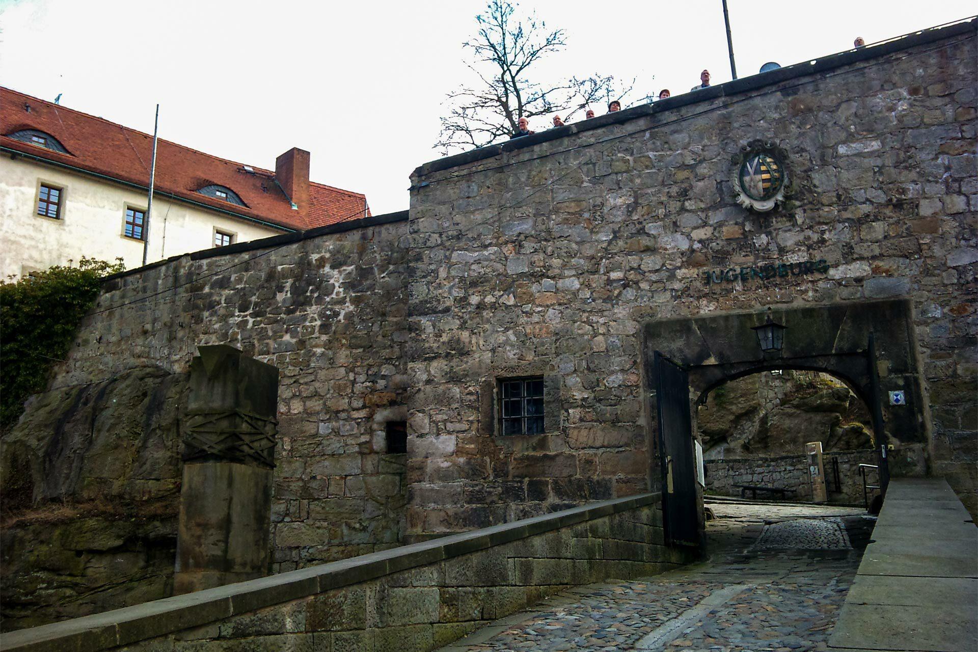 Durch den Schindergraben am Bärenzwinger vorbei geht es hinauf zur Burg Hohnstein, die gerade im Frühling immer mal wieder durch die Baumkronen blinkt.