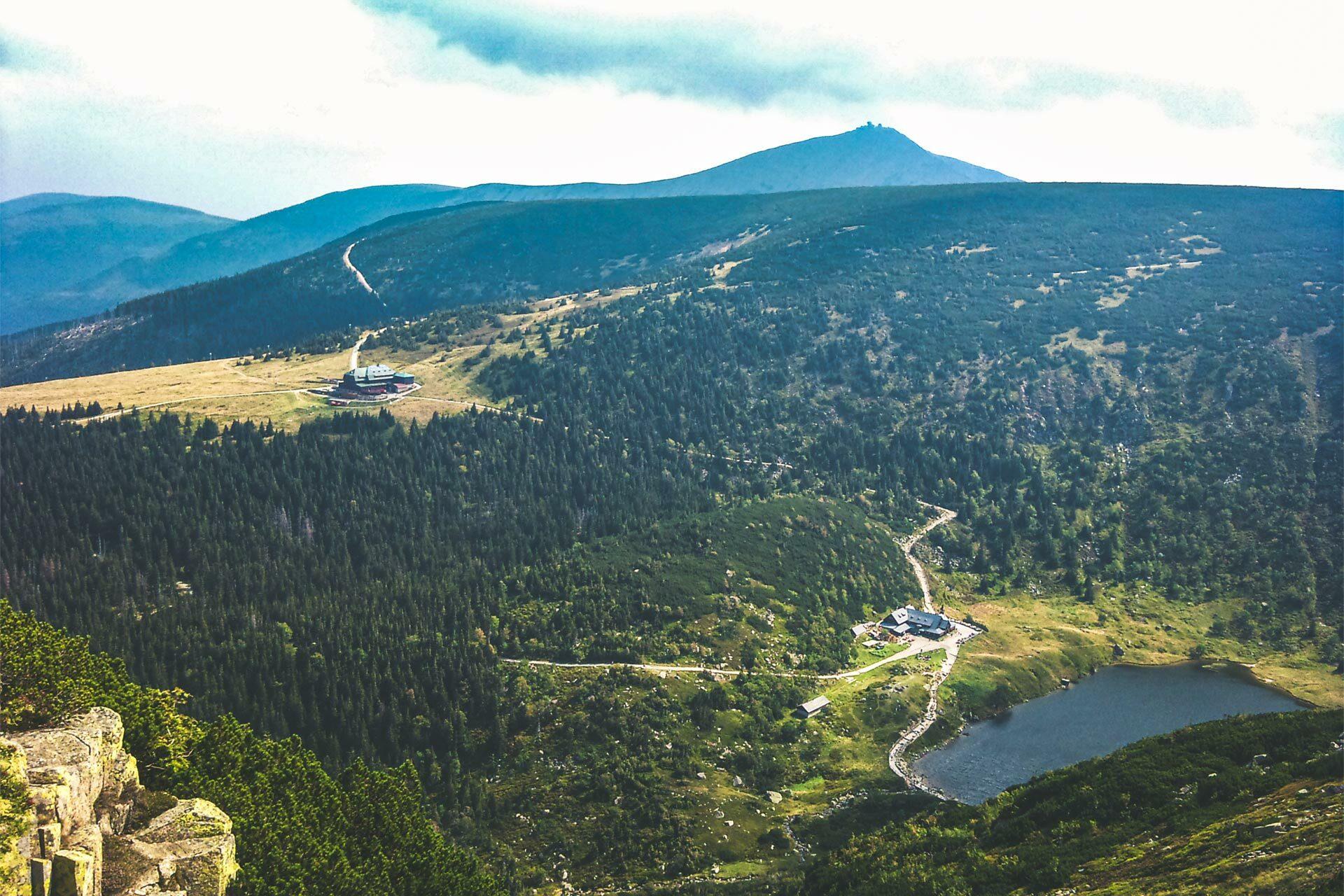 Steil ging es am Kammweg bergab. Hier die polnische Seite. Eine Hütte idyllisch am Bergsee gelegen.